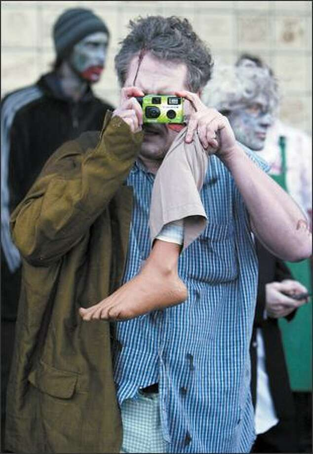 Dan Green of Seattle photographs fellow undead as they wait for the Zombie Walk to begin at University Village on Sunday. Photo: Meryl Schenker/Seattle Post-Intelligencer