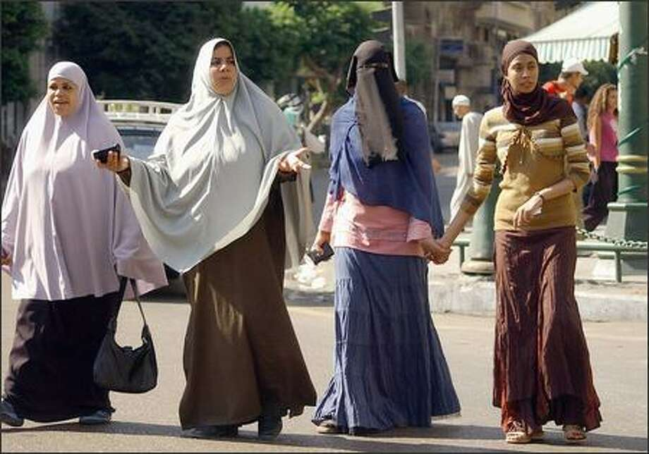 Muslim women cross a street in downtown Cairo. The third from left is wearing a niqab, which covers her face and leaves only a slit for the eyes. The niqab is the focus of a fierce debate in Egypt. Photo: / Associated Press