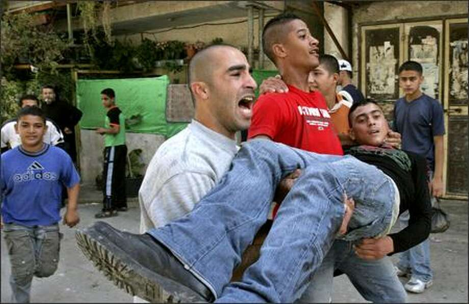 Palestinians carry a youth injured during clashes between Palestinians and Israeli troops in the West Bank refugee camp of Tulkarem on Wednesday. Israel took over the Gaza town of Beit Hanoun to halt the flow of weapons. Photo: / Associated Press