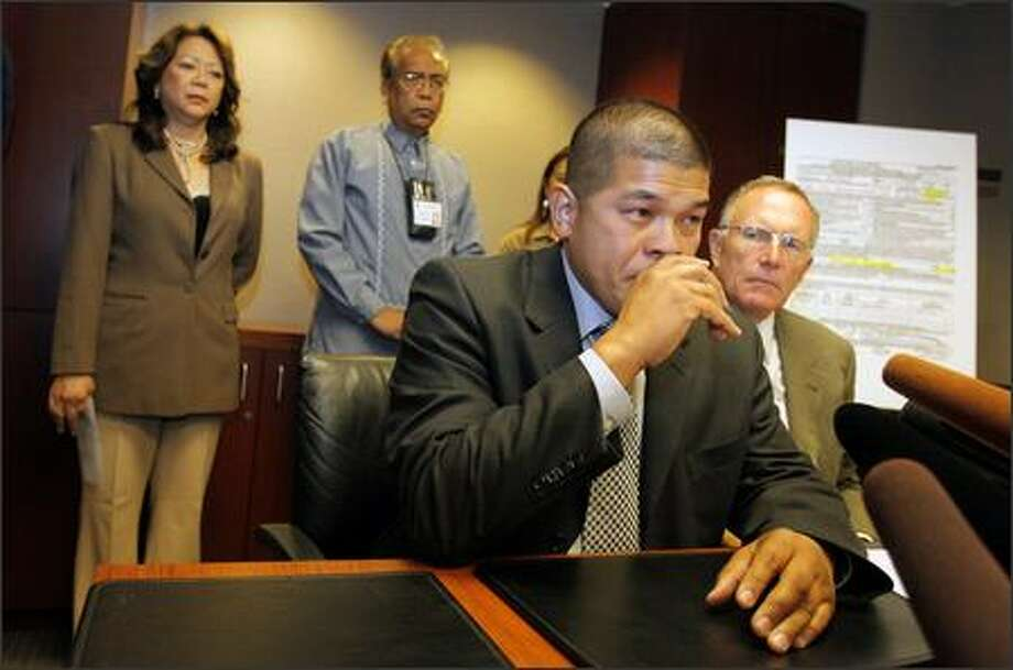 Ismael Ileto, foreground, talks about his brother at a news conference Thursday. Ileto is the brother of U.S. postal worker Joseph Ileto, slain in 1999. Attorney Mike Withey, right, represents the family of Joseph Ileto. In the background are Alma Kern, left, and Bert Caoili, both Filipino community leaders. Photo: Gilbert W. Arias/Seattle Post-Intelligencer
