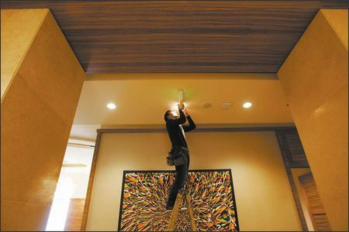 Art installer Tim Purtill of Atomic Arts Services adjusts a light that will illuminate a Michael Knutson painting in the lobby of the new Pan Pacific Hotel at the 2200 Westlake complex in Seattle Thursday, November 2 , 2006. (PHOTO MIKE KANE/ PI STAFF)