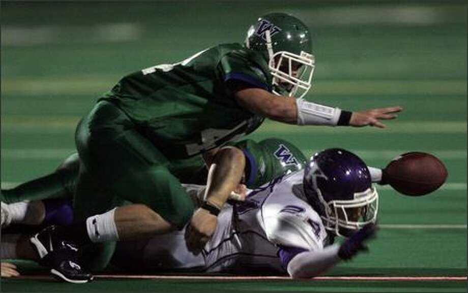 Woodinville's Steve Low reaches for the ball after a fumble by Kamiak's Justin Glenn in the second quarter. Low recovered the fumble. Photo: Mike Kane/P-I