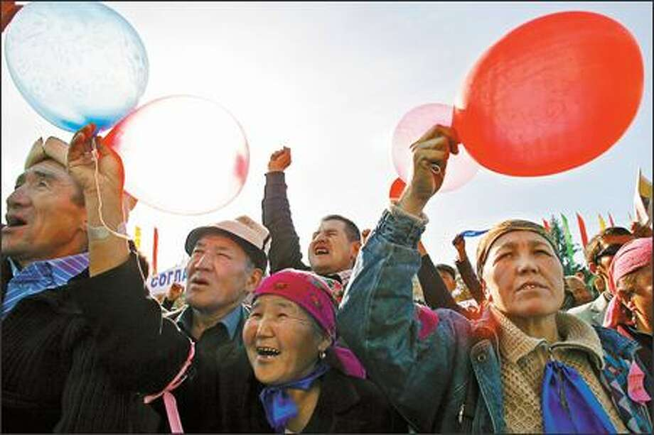 Supporters of Kyrgyzstan's president rally Wednesday at the parliament building in Bishkek. The amended constitution would trim the president's powers. Photo: / Associated Press