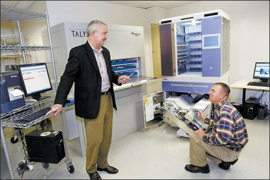 Talyst executives Tim McMenamin, left, and Michael Hymer show components of their pharmacy management system Thursday. Talyst is getting $20 million from venture capital firms. Photo: Grant M. Haller/Seattle Post-Intelligencer