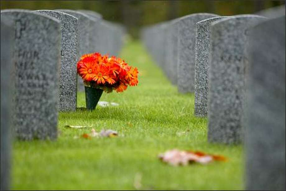 """Flowers decorate a grave in the cemetery's """"Section 6,"""" the area where soldiers killed in Afghanistan and Iraq are interred. Photo: Joshua Trujillo/Seattle Post-Intelligencer"""