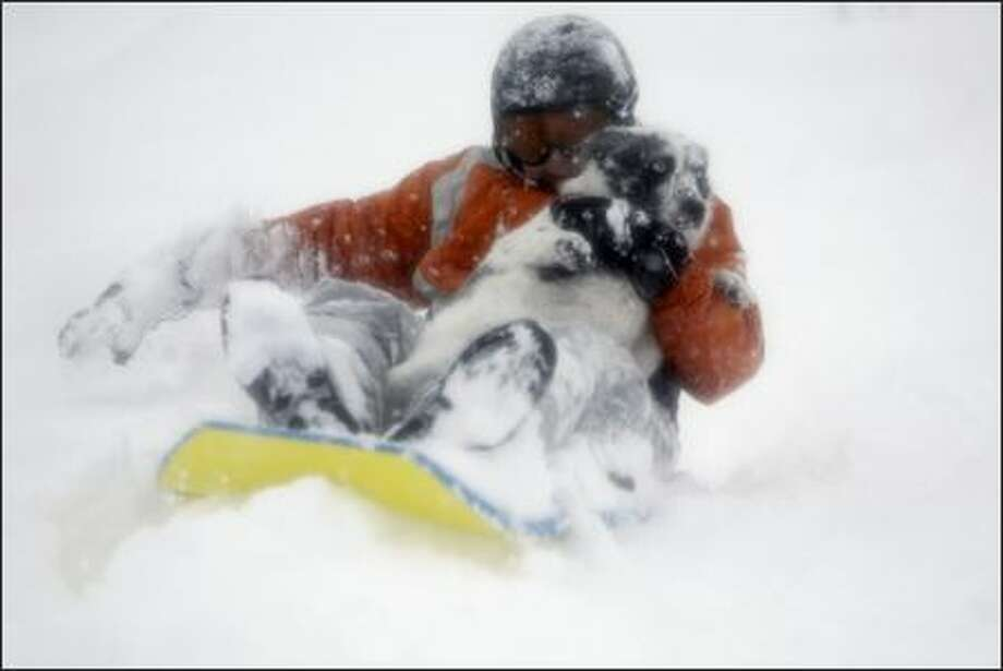 Kyle Gunderson, 12, and dog Kloey slide down a hill at Stevens Pass ski area Friday as his father, Frank, watches from above. Photo: ANDY ROGERS/P-I