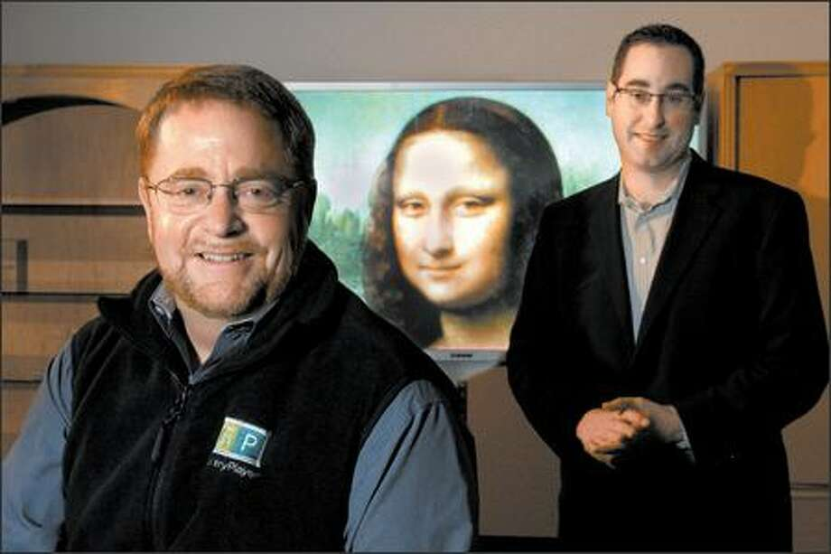 Rusty Citron, left, of GalleryPlayer and Tom Pierce of Comcast stand in front of an example of high-definition art for the television screen. Photo: Meryl Schenker/Seattle Post-Intelligencer