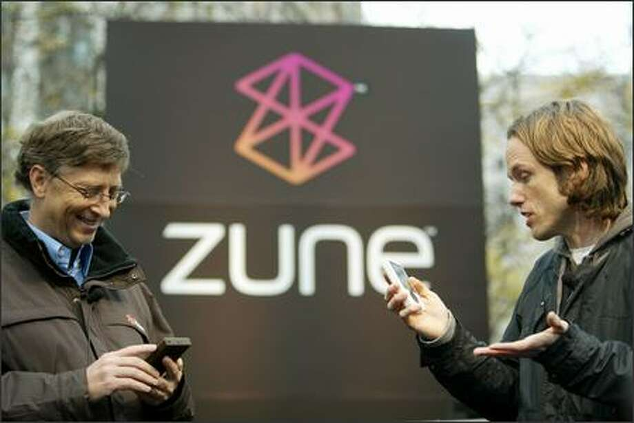 John Richards of Seattle radio station KEXP sends a song from his Zune to one held by Microsoft chairman Bill Gates by using the wireless sharing feature in the new music device at Westlake Park in Seattle on Monday. Photo: Dan DeLong/Seattle Post-Intelligencer