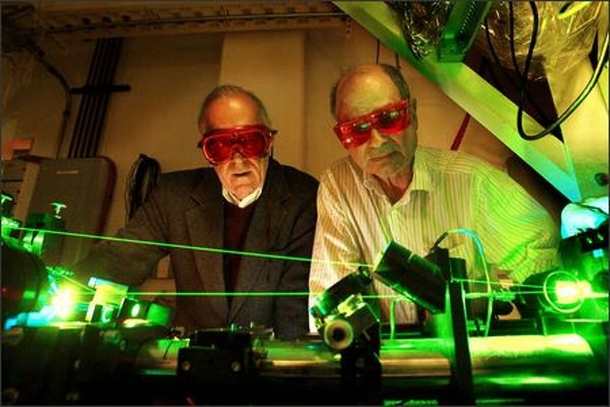 """Physicists John Cramer, left, and Warren Nagourney work in the lab. Nagourney says he has """"a faint understanding"""" of Cramer's idea."""