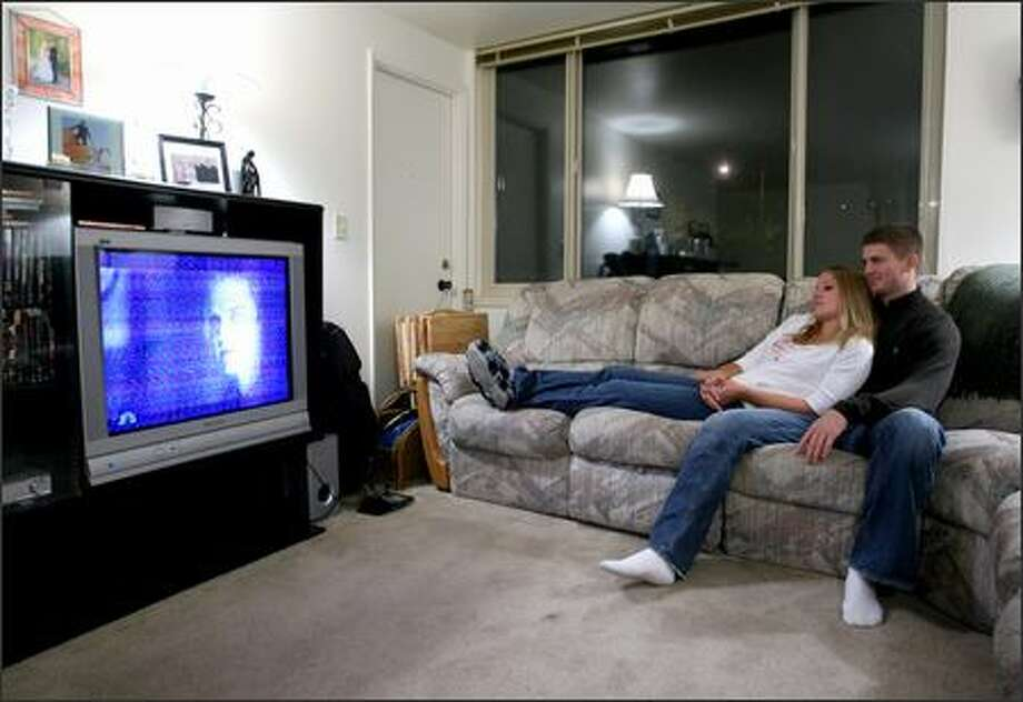 "Huskies quarterback Carl Bonnell relaxes with his wife, Katie, at their UW apartment, watching ""Friday Night Lights"" on their non-cable TV. The Bonnells met in junior high. Photo: Scott Eklund/Seattle Post-Intelligencer"