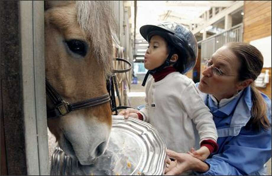 "Alex Wong, 5, blows a kiss to ""Bjorn"" as he feeds the horse carrots after a therapy session at the Little Bit Therapeutic Riding Center in Woodinville while his physical therapist, Debra Peet-Walker, lends a hand. Photo: Gilbert W. Arias/Seattle Post-Intelligencer"