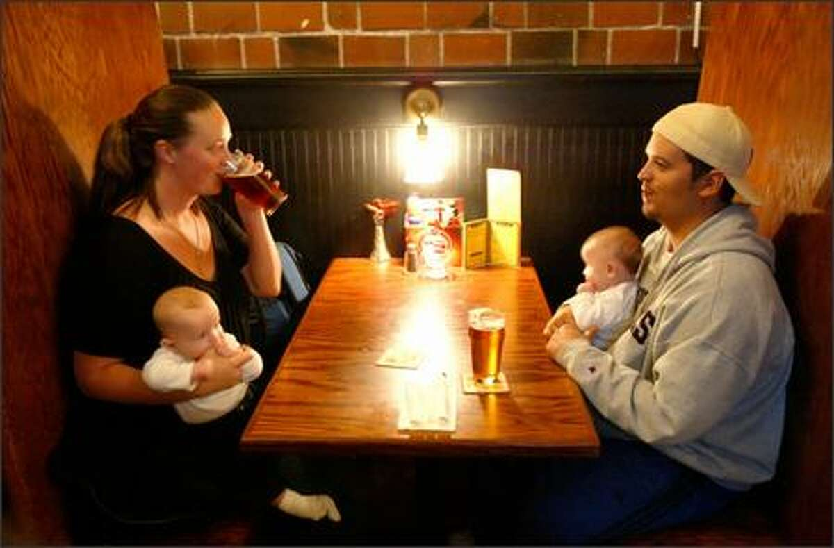 Oceania and Chaz Welsh enjoy a pair of pints and quality time with their twins, 4-month-old Nicolai, left, and Carlo, at the Elliott Bay Brewery Pub in West Seattle.