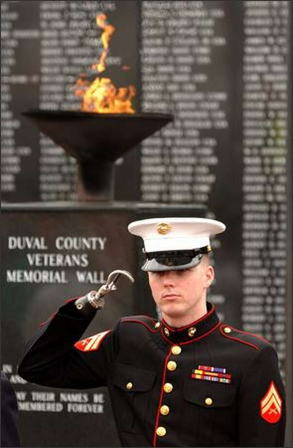 "Marine Cpl. James ""Eddie"" Wright salutes during a ceremony at the Jacksonville, Fla., Veterans Memorial Wall several months after an April 2004 firefight in Iraq. Wright was awarded a Bronze Star for valor for his actions.  (Bob Self/The (Jacksonville) Florida Times-Union) Photo: / Associated Press"
