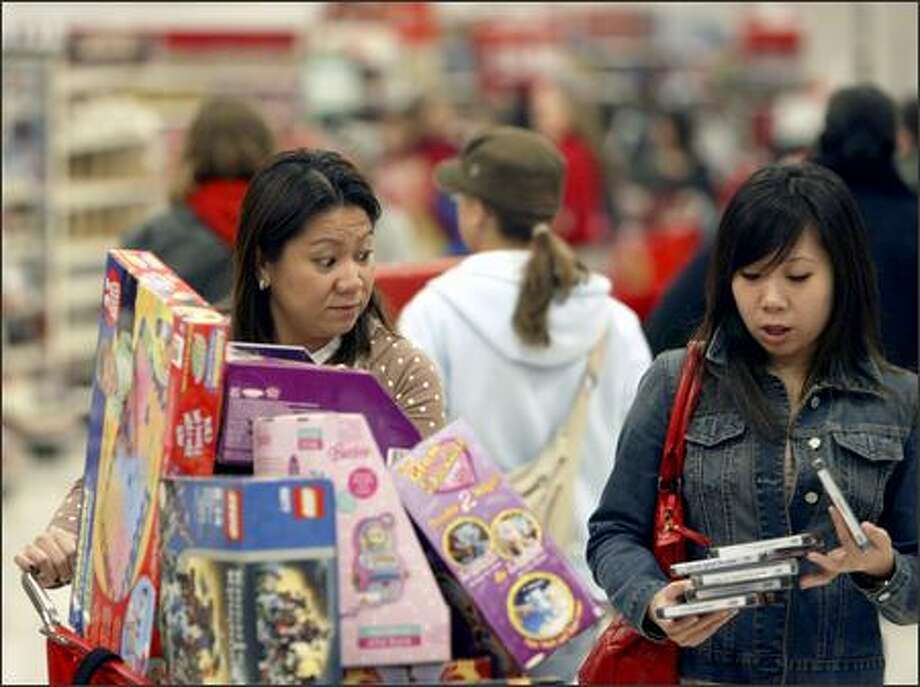 Mary, left, and Melissa Escalante compare their loot while walking through the Northgate-area Target shortly after the store's 6 a.m. opening. The day after Thanksgiving is one of the busiest shopping days of the year. Photo: Andy Rogers/Seattle Post-Intelligencer