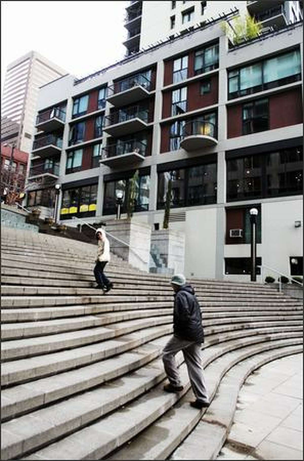 Pedestrians make their way up the Harbor Steps in downtown Seattle. While newer suburban developments are pedestrian-friendly, it's unpleasant or even dangerous to walk or bike from one to another or across town.