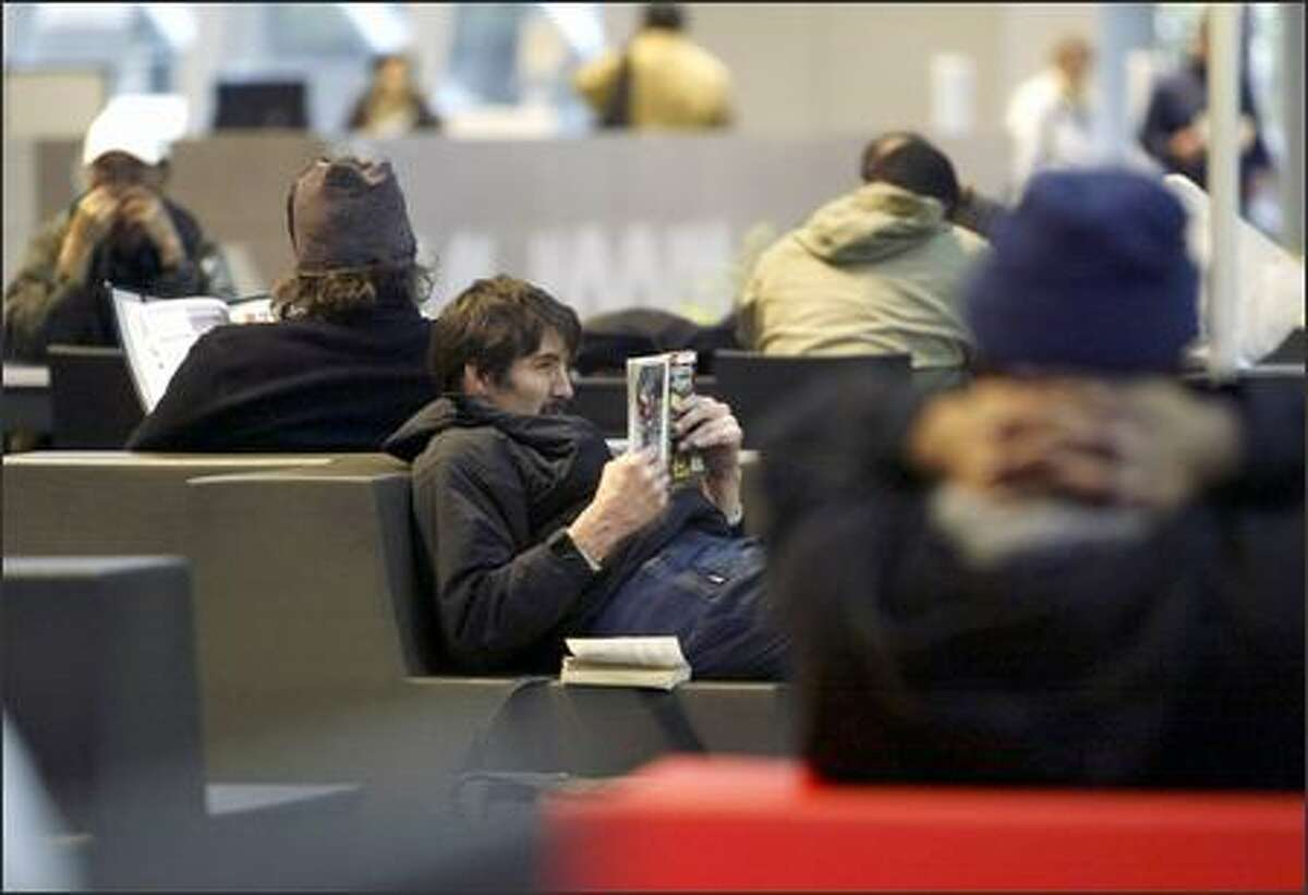 """Tiberious Shapiro takes a look at Reader's Digest in the """"Living Room"""" area of the Seattle Central Library recently. Shapiro says the downtown library is his favorite place to pass the time before homeless shelters open."""