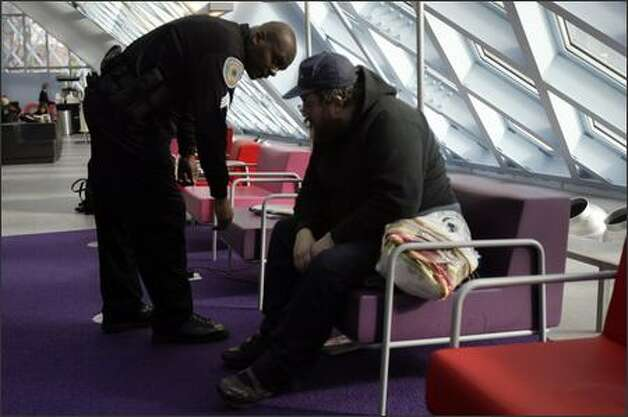 Security officer Christopher Hogan chats with Kevin Vanderhoef, who had nodded off at the library after spending a night on the street. Vanderhoef was reminded of the rules, which includes no sleeping. Vanderhoef says he visits the library frequently, sometimes every day Photo: Andy Rogers/Seattle Post-Intelligencer