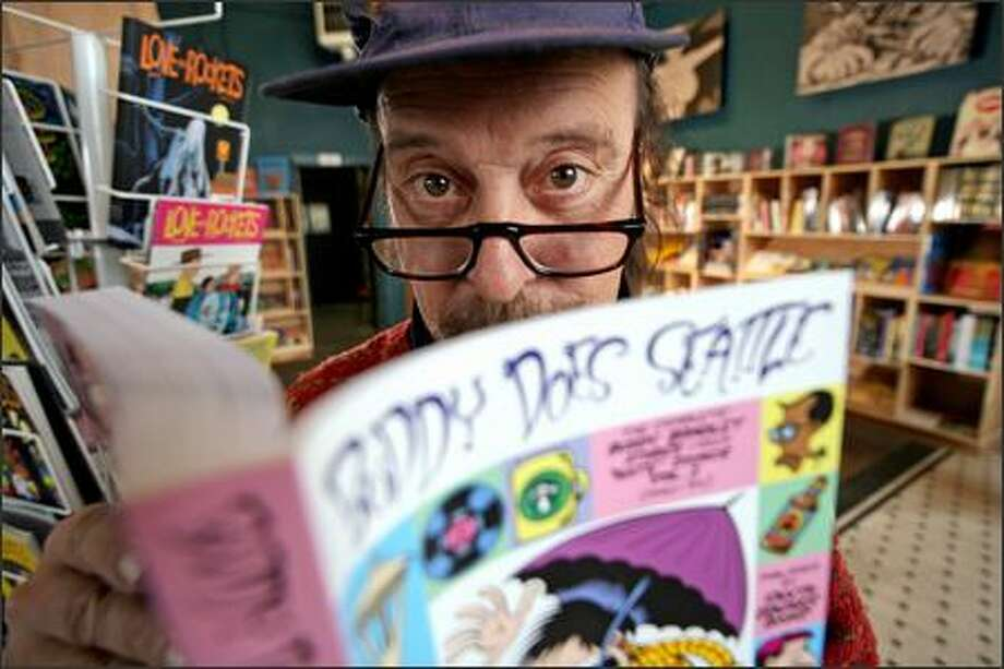 "Larry Reid, curator and events coordinator for Fantagraphics' new store, peers over a copy of ""Buddy Does Seattle"" by Peter Bagge. Photo: Grant M. Haller/Seattle Post-Intelligencer"