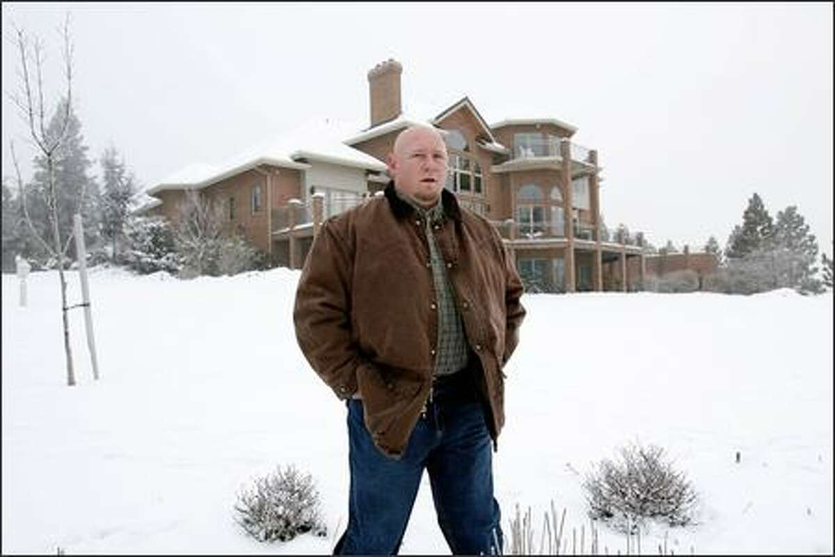 Steve Emtman, now a successful real-estate developer, stands outside his home in Spokane Valley. Emtman wants to see the football program restored to its dominant position in the UW athletic department.