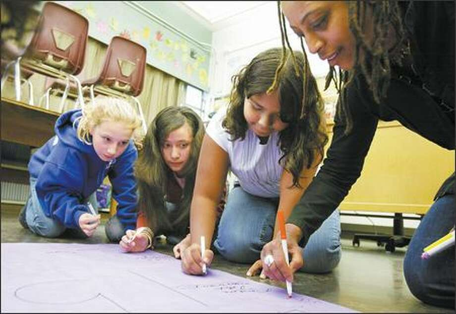 Powerful Voices counselor La Rond Baker, right, works on a giant birthday card with Michaela Montstream, left, Ingrid Amador Reyes and Darshana Jaint during a weekly session at Washington Middle School on Thursday. The Girls RAP program is helped by the Seattle P-I's Readers Care Fund. Photo: Gilbert W. Arias/Seattle Post-Intelligencer