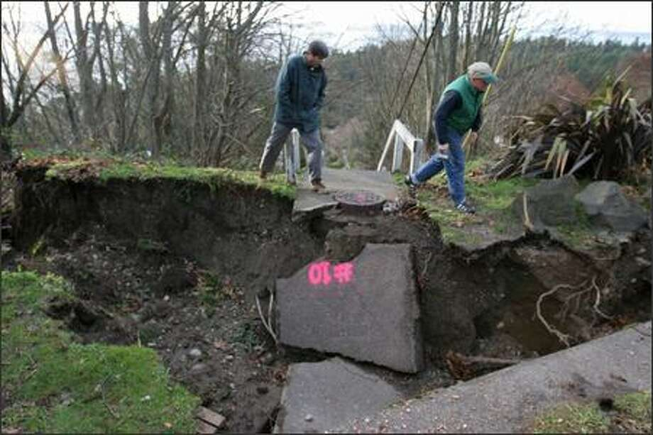 Moin Kadri, left, an engineering geologist, and Jim Jackson explore a 6-foot-deep sinkhole at the corner of Southwest Thistle and Northrop Place Southwest in West Seattle, which they believe contributed to a mudslide that ended in Jackson's backyard a few hundred feet away. Photo: Meryl Schenker/Seattle Post-Intelligencer