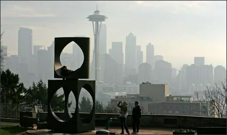 Haze covers Seattle as Michelle Chavez, center, photographs Jonathan Hopper in the sculpture at Kerry Park. Aaron Lum, right, watches. Many residents who still don't have power are burning wood to keep warm, which is causing regional air quality to worsen. Photo: Grant M. Haller/Seattle Post-Intelligencer