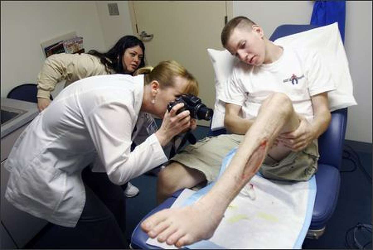 Wendy Vick, clinic nursing supervisor at Providence Everett Medical Center, takes pictures of Brett Karch's wounds. Karch, a member of the Snohomish High School ROTC team that was manning a cannon at a football game, nearly lost his leg when the cannon accidentally blew up. In the back is Karch's mom, Mary Bissel.