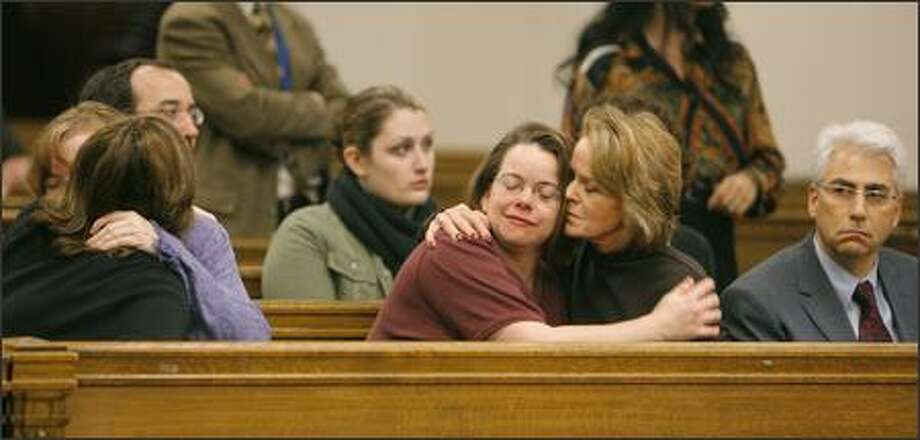 Ianthall Sidell, center right, former board member of the Jewish Federation of Greater Seattle, comforts Carol Goldman, center, one of six victims from last summer's shooting, during Wednesday's hearing. At left, victim Cheryl Stumbo is hugged by Robin Boehler, chairwoman. On the far right is Executive Director Richard Fruchter. Photo: Gilbert W. Arias/Seattle Post-Intelligencer