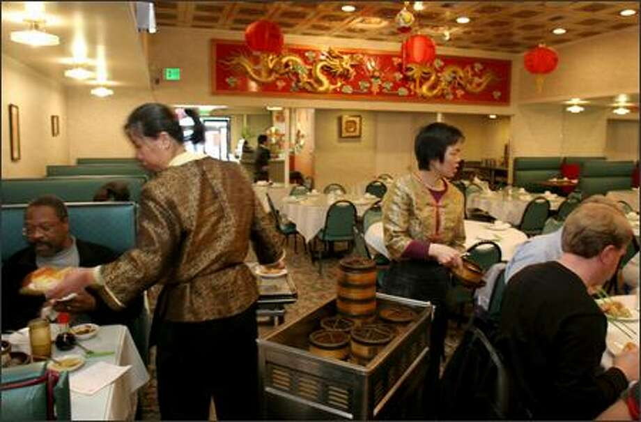 Rui Jin Jiang, left, and Lao Cui Yue serve dim sun at China Gate Restaurant in the International District. China Gate will be one of several Chinese restaurants that will be open for dinner on Christmas. Photo: Meryl Schenker/Seattle Post-Intelligencer