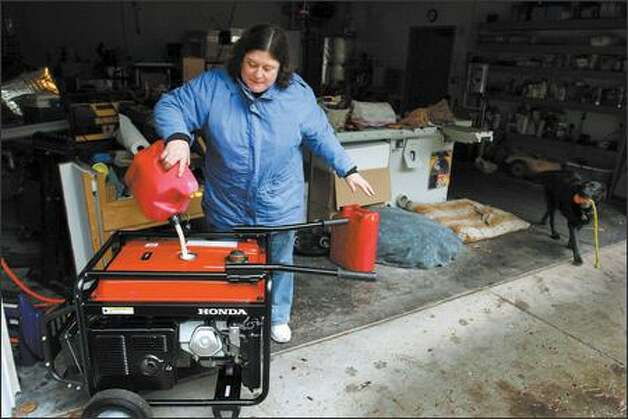 Alverna Palmer puts gasoline in the generator. The Carnation family finally saw the light Sunday night, when crews restored heat and light to the beleaguered community. Photo: Meryl Schenker/Seattle Post-Intelligencer