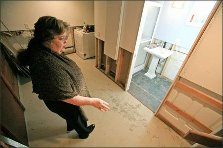 Jennifer Forrey points out flood damage to the newly renovated basement of the home she shares with Jack Lawless. Four feet of water filled the West Seattle basement during the rainstorm on Dec. 14. They plan to pursue claims against the city. Photo: Meryl Schenker/Seattle Post-Intelligencer