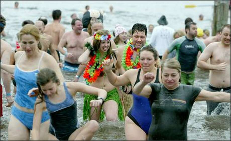 Heather Prenevost and Greg Bennett celebrated the New Year with hundreds of others less exotically attired at the fifth annual Polar Bear Plunge at Matthews Beach. Photo: Paul Joseph Brown/Seattle Post-Intelligencer