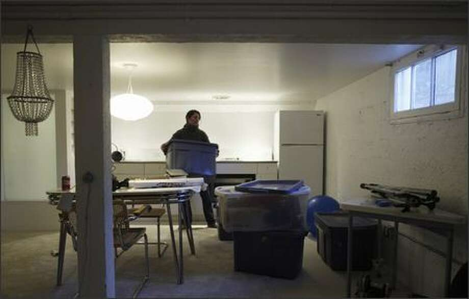 Randilyn Kealey moves around boxes in the basement of the house she and her fiancé, Mike Kimelberg, recently bought in Montlake. The couple plan to make the basement their master bedroom suite. Photo: Andy Rogers/Seattle Post-Intelligencer