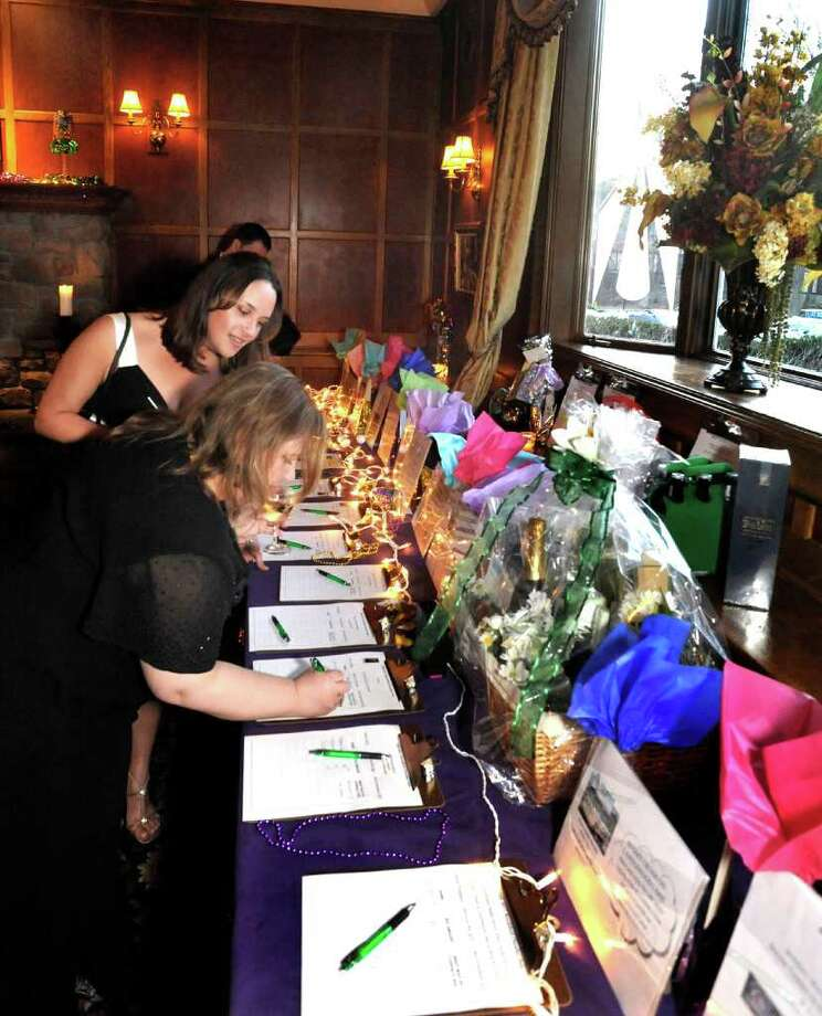 Guests look over the auction items during the Mardi Gras Gala, hosted by the Brookfield Chamber of Commerce. The event was held at The Fox Hill Inn in Brookfield, Saturday, March 19, 2011. Photo: Michael Duffy / The News-Times
