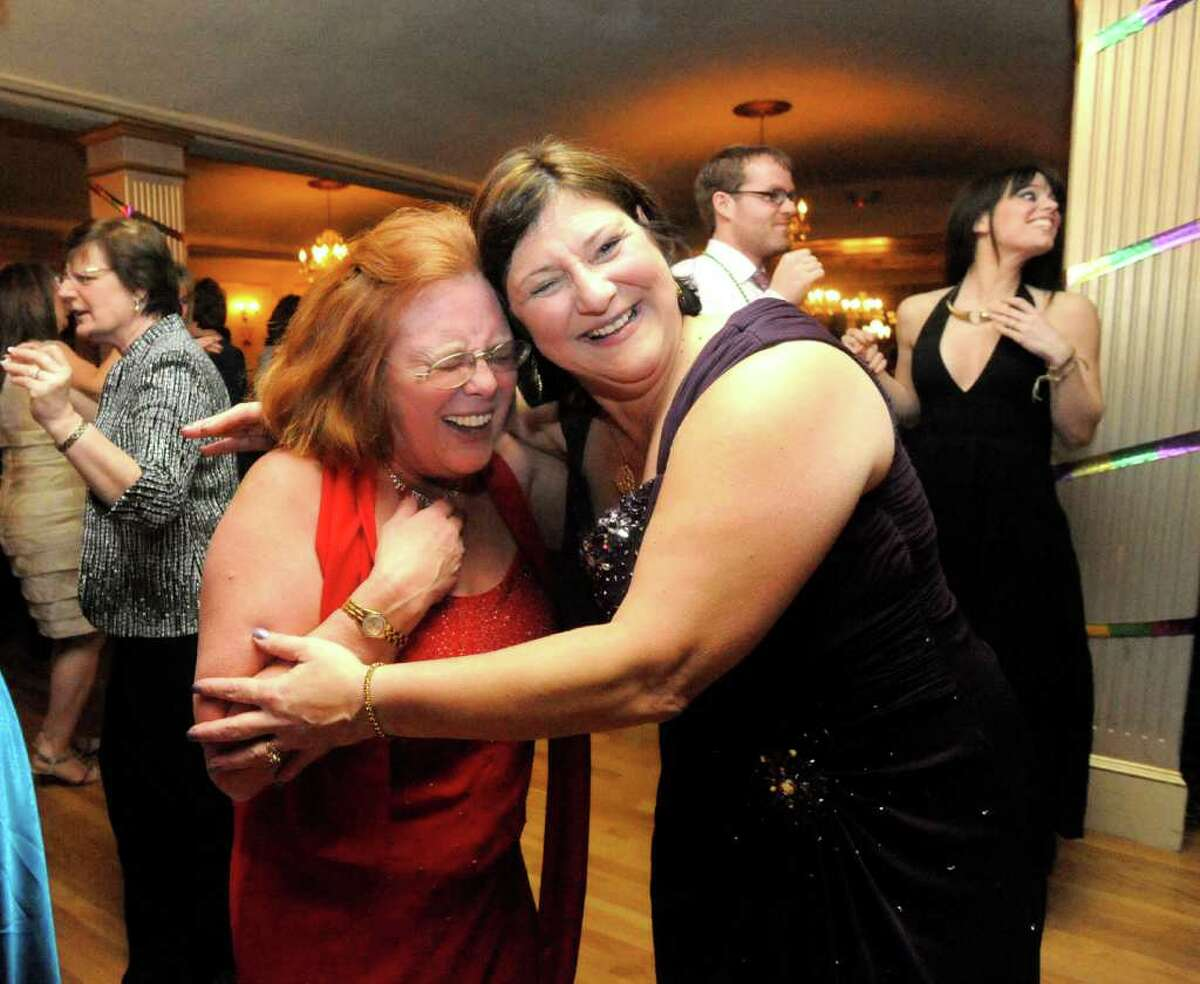 Judy Abdella, left, and Linda Wagner, center, share a moment during the Mardi Gras Gala, hosted by the Brookfield Chamber of Commerce. The event was held at The Fox Hill Inn in Brookfield, Saturday, March 19, 2011.