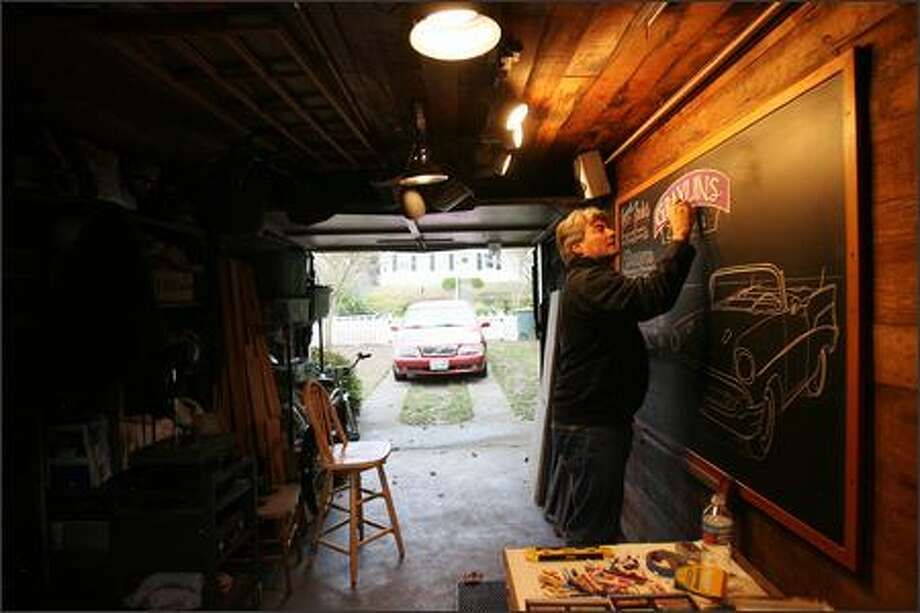 "John Rozich illustrates a chalkboard for a Detroit restaurant in his Magnolia ""studio,"" the garage. Classic cars are one of his favorite subjects. Photo: MIKE URBAN/P-I"