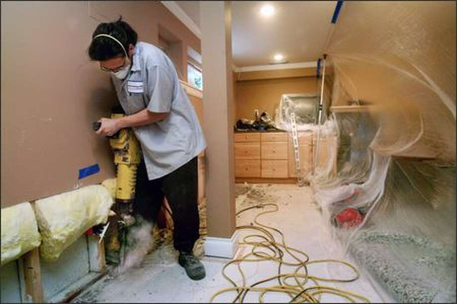 Susan Bithell first noticed flooding in the basement of her Mount Baker home in November, but repair work on it didn't begin until Friday. Jason Ando, with Aqueous Basement Systems, uses a jackhammer to install a drainage system. Photo: Dan DeLong/Seattle Post-Intelligencer