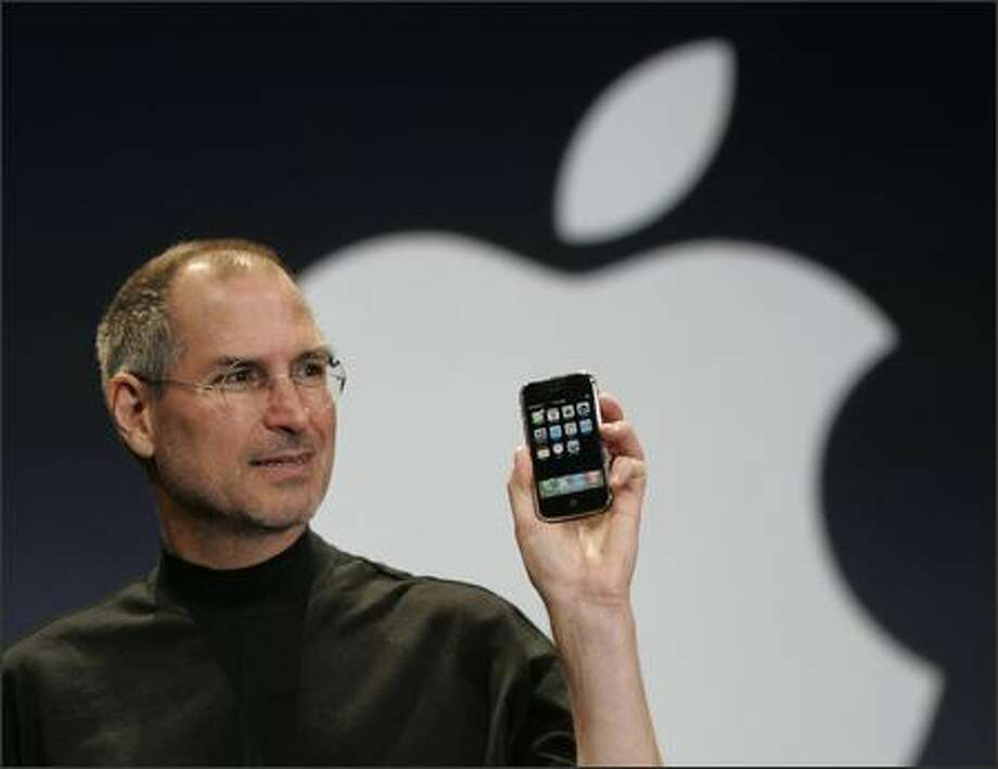 Apple CEO Steve Jobs holds up the new iPhone during his keynote address at the MacWorld Conference & Expo in San Francisco. (AP Photo/Paul Sakuma) Photo: / Associated Press