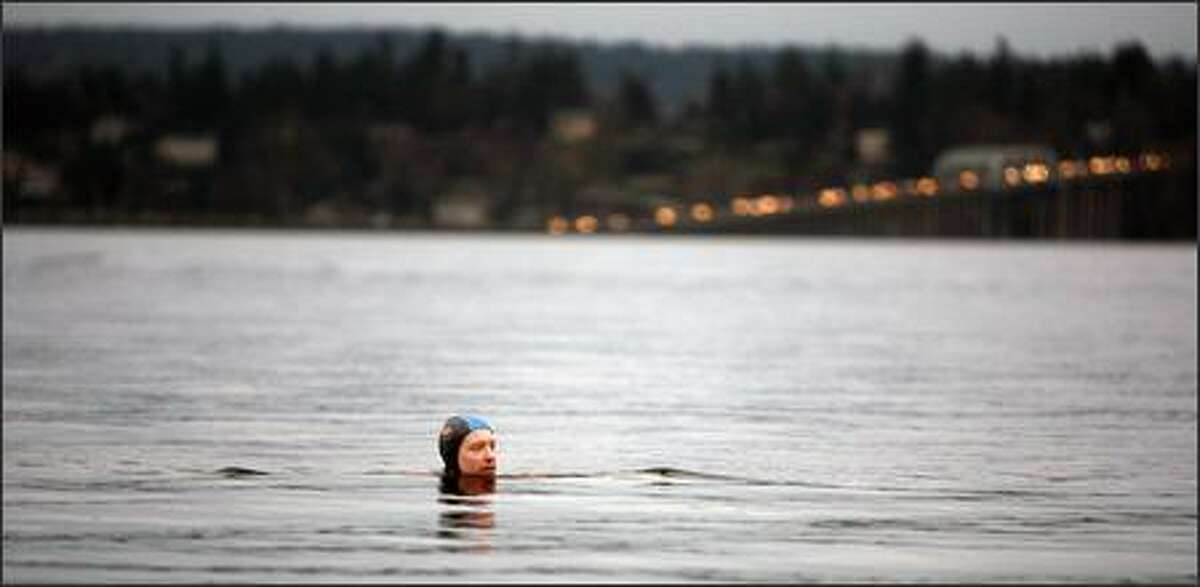 Michael Sullivan takes a dip at dusk on Monday, with the 520 Bridge in the background. This fall and winter he has gone swimming in some of the most stormy local weather on record, including snowfalls.