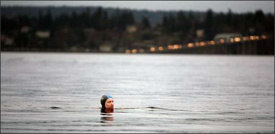 Michael Sullivan takes a dip at dusk on Monday, with the 520 Bridge in the background. This fall and winter he has gone swimming in some of the most stormy local weather on record, including snowfalls. Photo: Scott Eklund/Seattle Post-Intelligencer