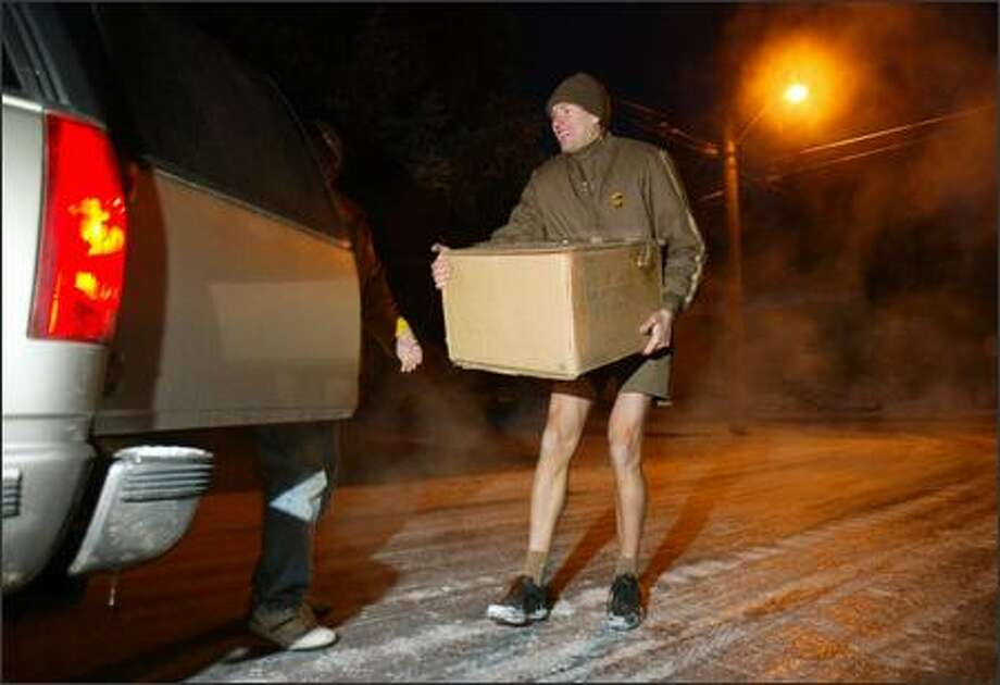 Though they may not be used to the snow and ice, most Seattleites slog to work even during bad weather. UPS deliveryman Brian Lee picks up a package delivered to his truck for a customer whose road was too icy in Meridian Park. Photo: Karen Ducey/Seattle Post-Intelligencer