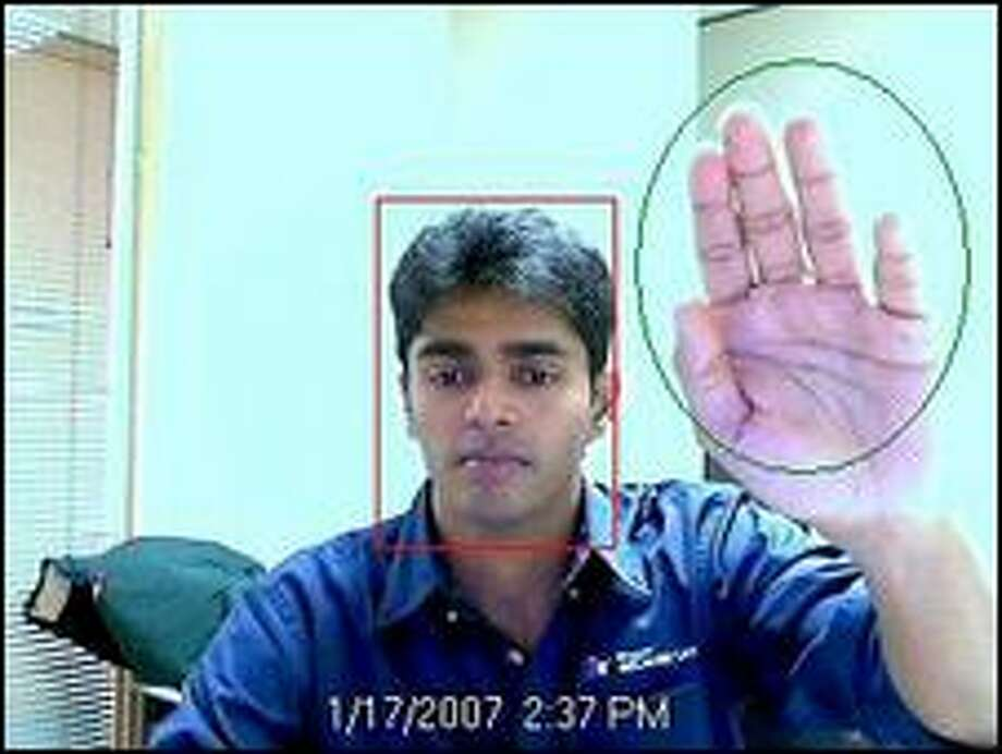 Rohan Shetty, a research software design engineer in Microsoft's adCenter Labs, demonstrates a program that uses a camera to try to identify a person's gender, based on common facial characteristics, to target advertising appropriately. Photo: / Microsoft