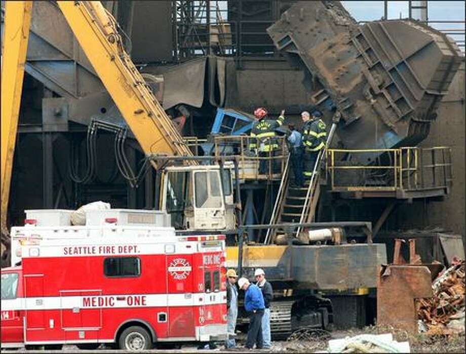 Firefighters and a police officer inspect an industrial shredder at the Seattle Iron & Metals Corp., where a worker was killed and two were injured in an accident Wednesday. Photo: GRANT M. HALLER/P-I