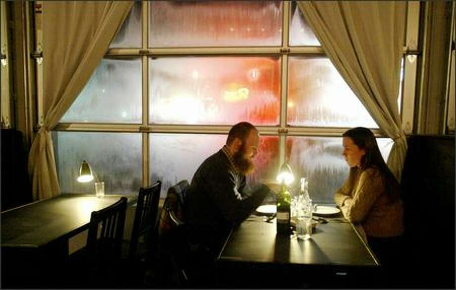 Gavin Tierney and Susan Knightly sit next to steamy glass doors at The Station Bistro, a renovated Ballard service station where most dishes are a bargain at $9 a pop. The food falls into a category somewhere between pub grub and epicurean. Photo: Gilbert W. Arias/Seattle Post-Intelligencer