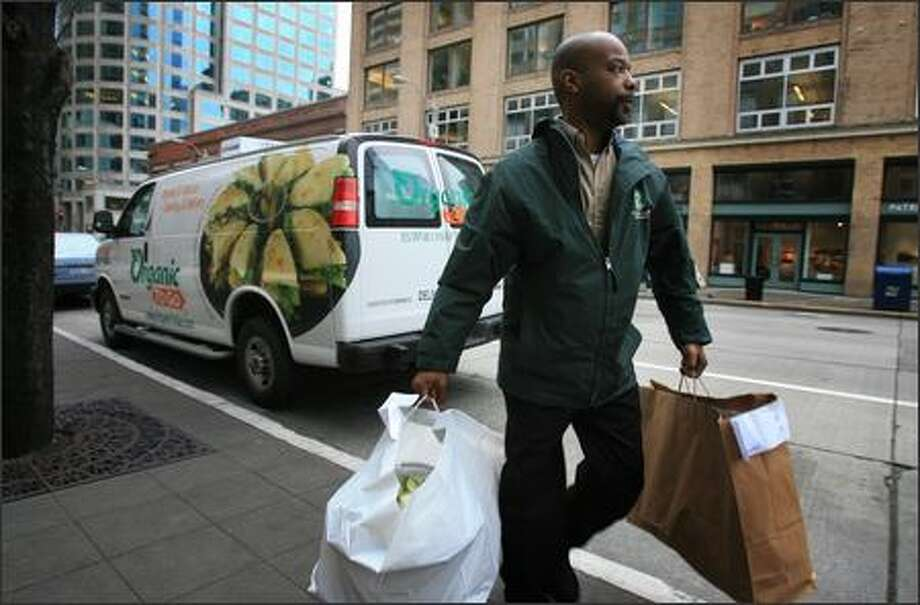 Organic To Go employee John Wheeler makes a lunch delivery in downtown Seattle. The company has cafes and offers catering from Western Washington to Southern California. Photo: Dan DeLong/Seattle Post-Intelligencer