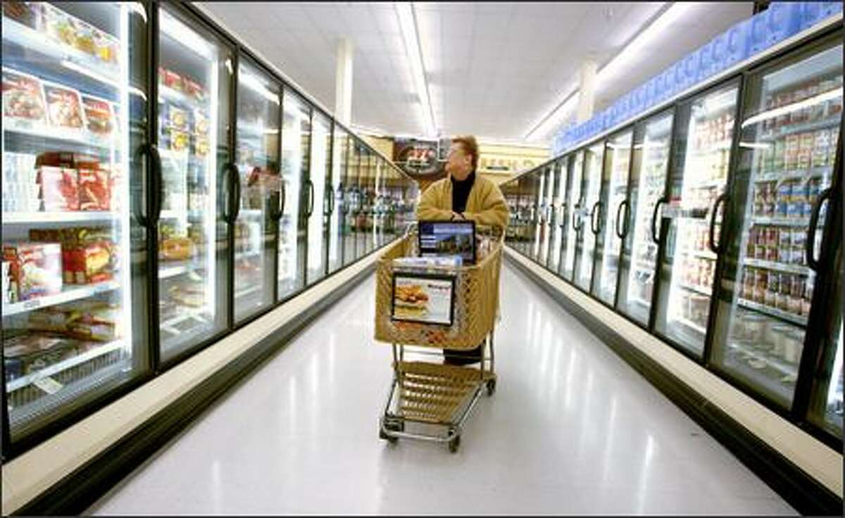 Bobbie Cook checks out the frozen food aisle during her shopping trip at the Safeway in Rainier Valley. Cook, who lives on a fixed income, is particularly interested in the issue of food availability and affordability. She shops at three different stores in Rainier Beach and is selective about what she buys.