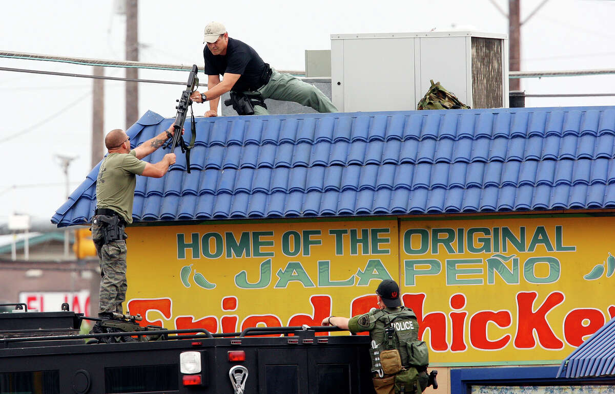 Members of the SAPD SWAT team work the scene of a standoff at the Rodeway Inn.