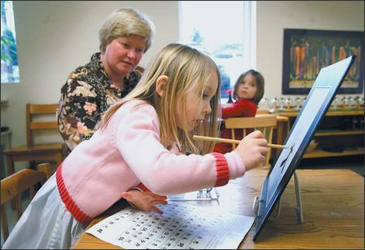 As teacher Jan Kamischke looks on, 5-year-old Ella McFarlane draws a kanji symbol at Pacific Crest School, a 21-year-old Montessori school on the fringe of Fremont. Kanji is a Japanese system of writing based on ideographic characters borrowed from the Chinese around the third century.