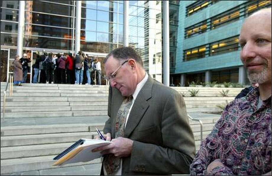 Plaintiffs' lawyer Michael Withey phones results of the verdict to the news media Tuesday as client Kenneth Hankin looks on at the federal courthouse in Seattle. A jury decided that the arrests of 147 people in the WTO protests didn't violate free-speech rights but did breach their right to be free of improper search and seizure. Photo: Karen Ducey/Seattle Post-Intelligencer