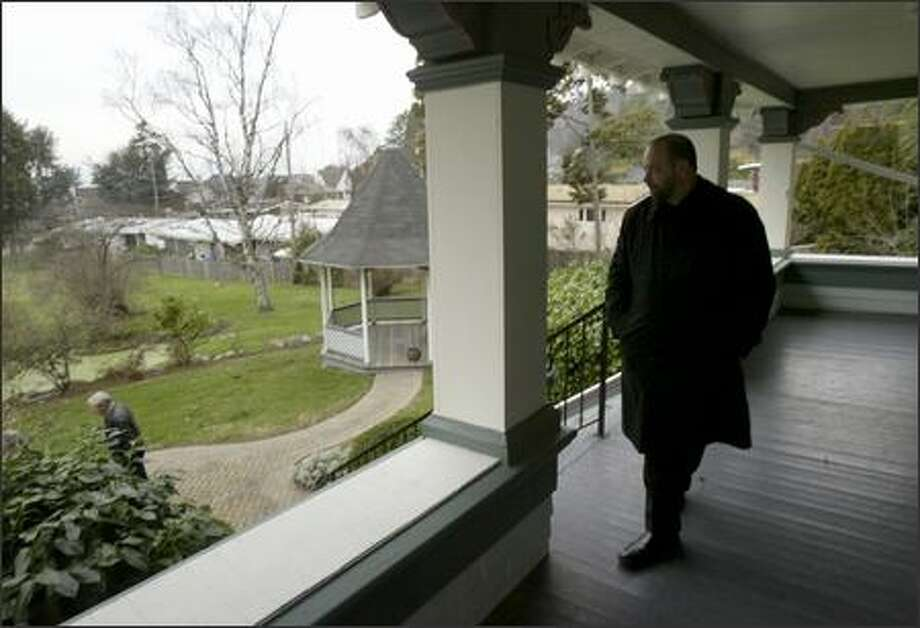 Fred Iacolucci, selling agent for the Satterlee House at 4866 Beach Drive S.W. in West Seattle, looks on from the porch as Tom Pozarycki of Scottsdale, Ariz., leaves after a tour of the home Monday. The house, a classic, Seattle-box style residence, is a historic landmark that is on the market for $995,000. Photo: Andy Rogers/Seattle Post-Intelligencer